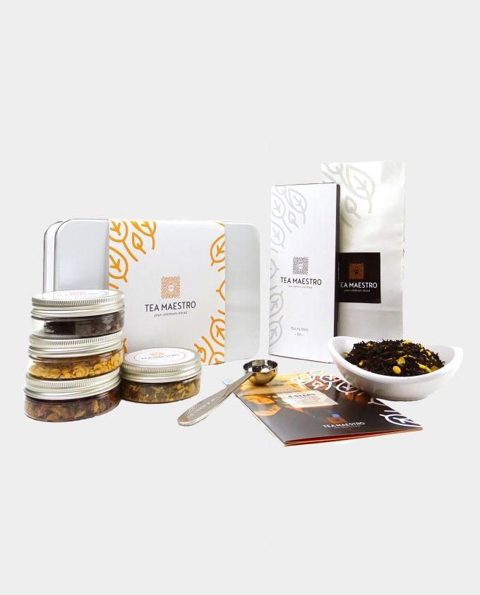 Thee geschenkset met zwarte thee sinaasappel, vier smaakmakers, een thee maatlepel, een doosje met theefilters en een instructiekaart.