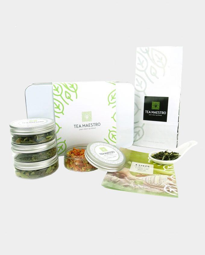 Theeblik gevuld met groene thee, vier smaakmakers en een instructiekaart.