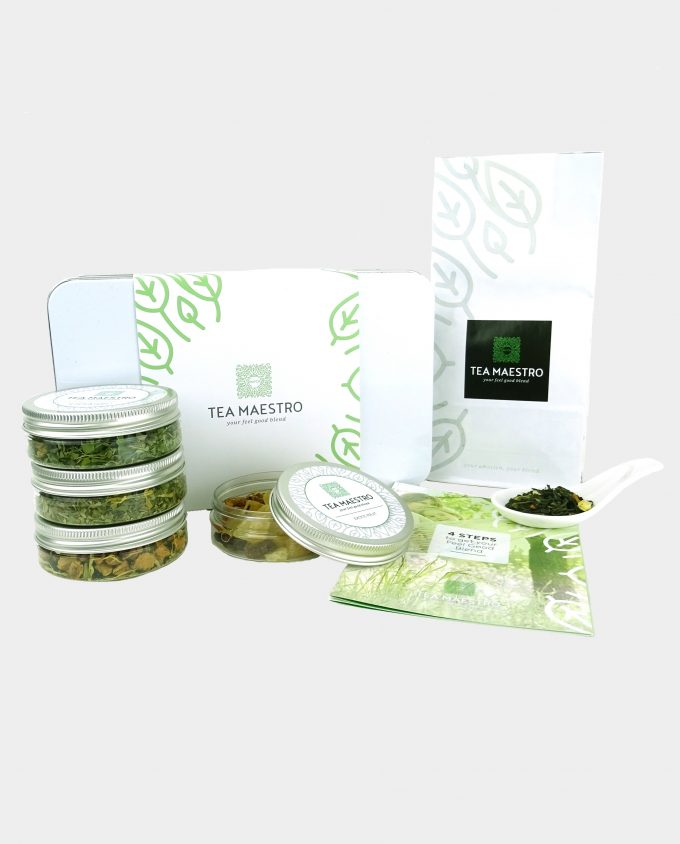 Theeblik gevuld met witte en groene thee, vier smaakmakers en een instructiekaart.