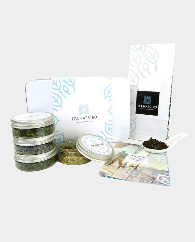 Thee geschenkset met vier soorten theeblikjes, één theezakje met groene thee, een thee maatlepel, een doosje met theefilters en een instructiekaart.