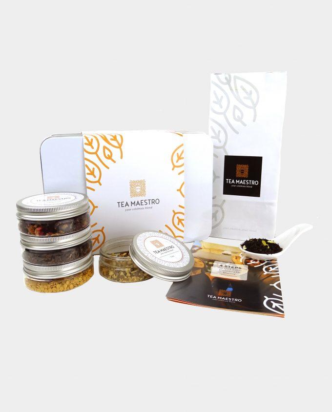 Thee geschenkset met vier soorten theeblikjes, één theezakje met zwarte thee, een thee maatlepel, een doosje met theefilters en een instructiekaart.