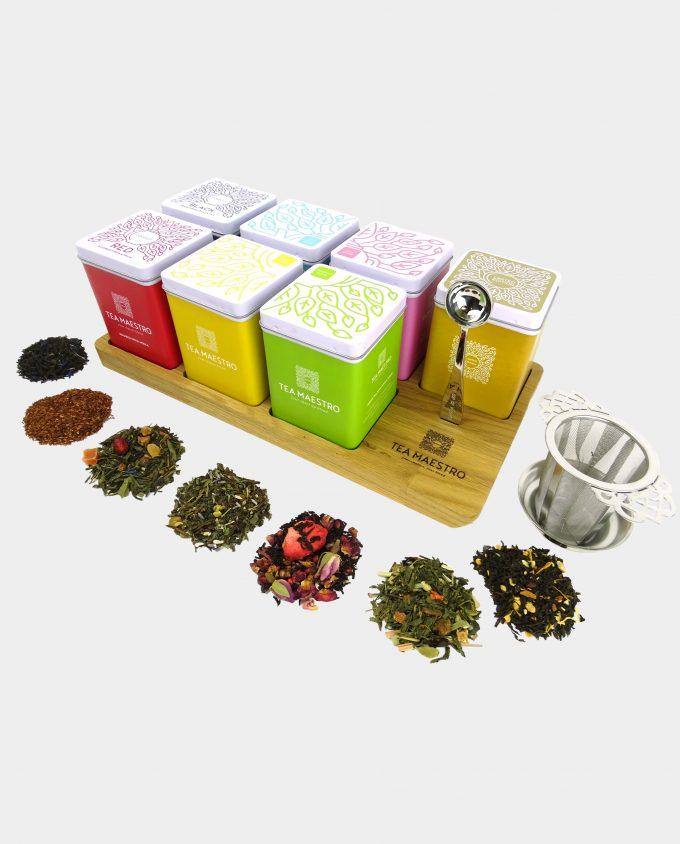 Thee blikjes met losse thee kruiden op eiken plateau